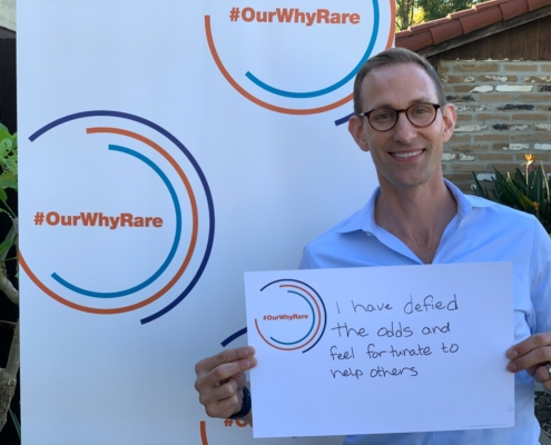 """CEO Eric Dube shows poster that says """"I have defied the odds and feel fortunate to help others""""."""