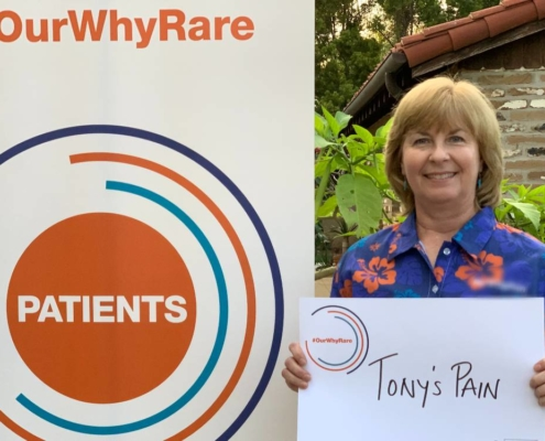 """Kathy holds a sign that says, """"Tony's Pain""""."""