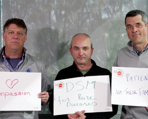 Employees hold posters that say why working in rare disease is important to them