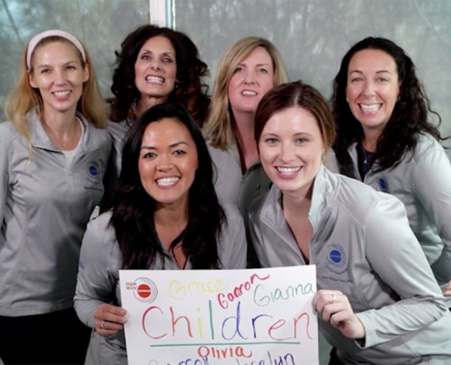 HR Team holds a poster describing the children for whom they work in rare disease